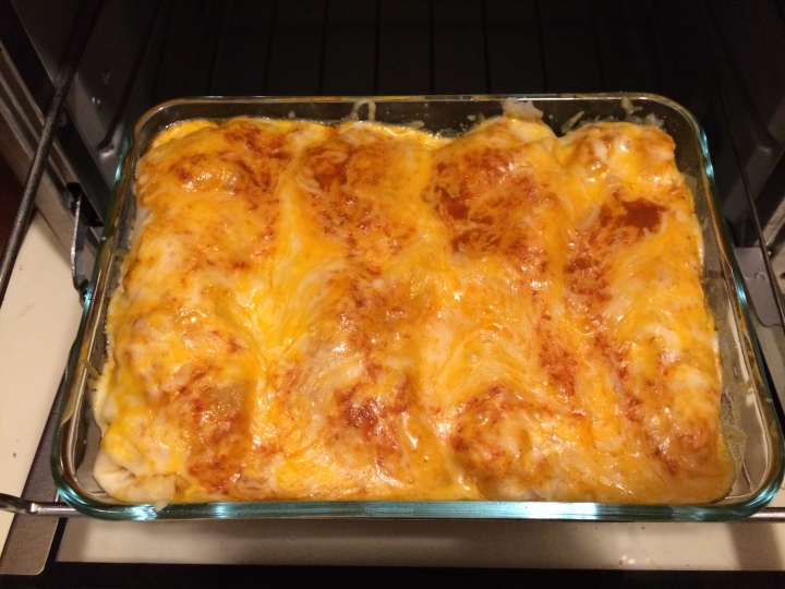 Half of a tray of chicken enchiladas once baked.